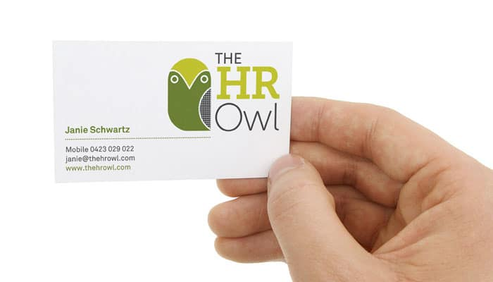Hand holding business card for The HR Owl Brand